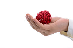 Spool of thread in hand. Hand holding a red spool of thread  on a white background Royalty Free Stock Photo