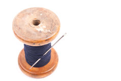 Spool of thread with needle. Big vintage spool of thread with needle isolated on white. Symbol of handmade, clothes and needlework Stock Photography