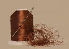 Spool of thread and needle closeup,isolated on light brown  bac. Kground Stock Images