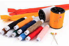 Spool of thread with needle, pins, zippers colorful sewing bobbin thread. Royalty Free Stock Photos