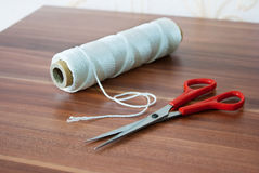 Spool of thread with scissors Stock Images