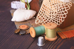 Spool of thread, a thimble and a box with needlework Stock Images
