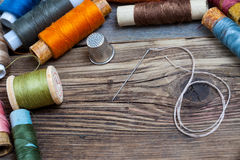 Spool of thread, a thimble and a sewing needle Royalty Free Stock Photography