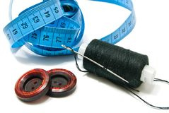 Spool of thread, two buttons and meter Royalty Free Stock Photo