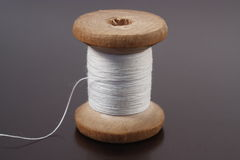 Spool of thread. Spool of white thread on a gray Royalty Free Stock Photos