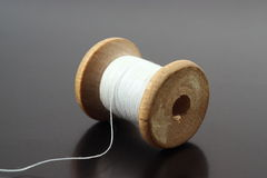 Spool of thread. Spool of white thread on a gray Royalty Free Stock Photography