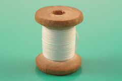 Spool of thread. Spool of white thread on a green Stock Photos