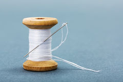 Spool of white sewing thread and needle Royalty Free Stock Photography