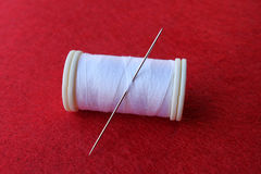 Spool white thread. And needle in red background Stock Photos