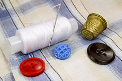 A spool of white thread with a needle, colored buttons and a thimble on the background of the shirt Stock Images