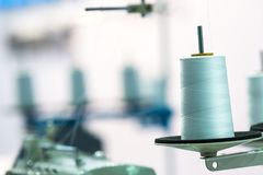Spool of white threads on sewing machine, closeup. Cloth factory, weaving, textile production, clothing industry Stock Photo