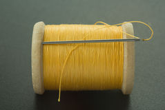 Spool with yellow thread and needle Stock Image