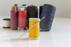 Spool Of Yellow Thread With Needle On The White Glossy Table stock photography