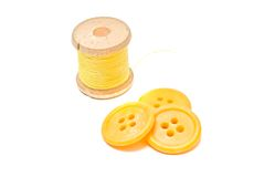 Spool of yellow thread and plastic buttons Stock Image