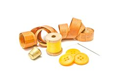 Spool of yellow thread, thimble and yellow buttons Stock Photo