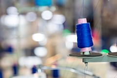 Spools of blue threads on sewing machine, factory. Spools of blue threads on sewing machine closeup. Cloth factory, weaving, textile production, clothing Royalty Free Stock Images
