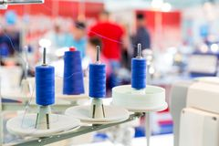 Spools of blue threads on sewing machine, closeup. Cloth factory, weaving, textile production, clothing industry Royalty Free Stock Photography