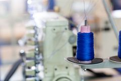 Spools of blue threads on sewing machine, factory. Spools of blue threads on sewing machine closeup. Cloth factory, weaving, textile production, clothing Stock Images
