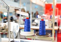 Spools of blue threads on sewing machine, factory. Spools of blue threads on sewing machine. Cloth factory, weaving, textile production, clothing industry Stock Photography