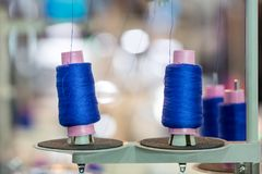 Spools of blue threads on sewing machine, factory. Spools of blue threads on sewing machine closeup. Cloth factory, weaving, textile production, clothing Royalty Free Stock Photo
