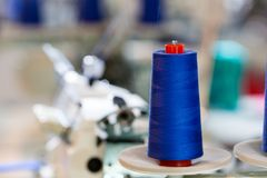 Spools of blue threads on sewing machine, factory. Spools of blue threads on sewing machine closeup. Cloth factory, weaving, textile production, clothing Stock Photo