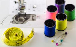 Spools of colored thread the tape, the needle on the sewing machine. Closeup royalty free stock photos