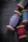 Spools of colored threads on vintage wooden board Royalty Free Stock Photo