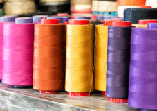 Spools of Colorful Cotton Thread on Metal Shelf. Textile Still Life - Close Up of Industrial Size Spools of Cotton Thread in Vibrant Colors of Pink, Orange Royalty Free Stock Photo