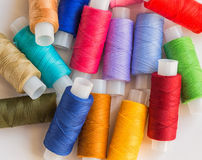 Spools of colorful thread. Colorful spools of thread pile on white Royalty Free Stock Photo