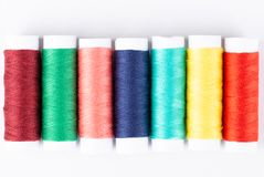 Spools of colorful threads in a row. Closeup Royalty Free Stock Image