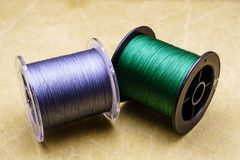 Spools of cords on the background of tarpaulin. Green and gray fishing line. Spools of braided fishing line. Spools of cords on the background of tarpaulin stock photo