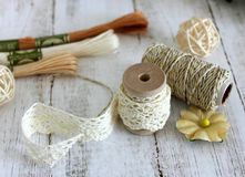 Spools with lace trim and baker`s twine. Laces and trims. Crafting and sewing supplies. Embroidery threads. Cream and brown shades royalty free stock image