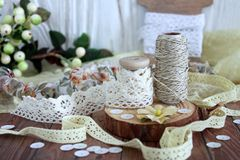 Spools with lace trim and baker`s twine. Laces and trims. Crafting and sewing supplies. In shabby chick style stock images