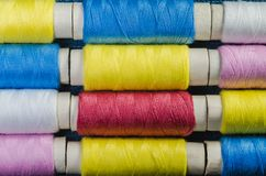 Spools of multi-colored threads arranged in rows stock photos