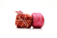 Spools of pink and brown thread and needle isolated on white background Stock Photography