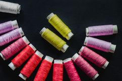 Spools of pink, red, white and yellow threads on black fabric royalty free stock photos