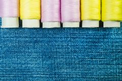 Spools of pink and yellow sewing thread on blue denim with copy space royalty free stock photography