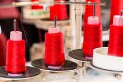 Spools of threads on sewing machine, cloth fabric. Spools of red threads on sewing machine. Cloth fabric, weaving, textile production, clothing industry Royalty Free Stock Images