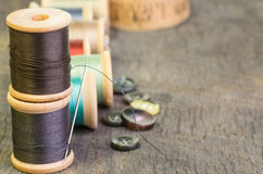 Spools of sewing theead with buttons. A stack of sewing thread spools with needle and buttons Stock Photos