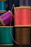 Spools of Thread. Close-up of stack of wooden spools with colorful thread and needle Royalty Free Stock Photo