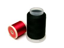 Spools of thread. Red and Black spools of thread over white background Stock Image