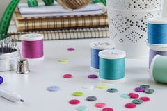Spools of thread and basic sewing tools including pins, needle, a thimble and buttons. Copy space royalty free stock photos
