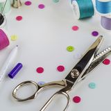 Spools of thread and basic sewing tools including pins, needle, a thimble and buttons. Copy space stock photos