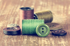 Spools of thread and buttons on wooden background Stock Photos