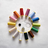 Spools of thread in circle with needle thimble and button Royalty Free Stock Photos
