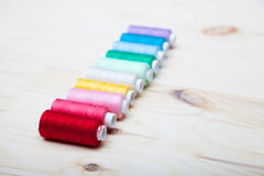 Spools of thread. Colorful spools of thread on a wooden background Stock Photos