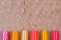 Spools of thread line the bottom of burlap Stock Photography
