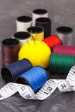 Spools of thread, needle and centimeter. Accessories for embroidery and sewing. Spools of colorful thread, needle and centimeter. Accessories for sewing stock image