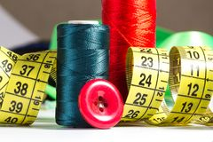 Spools of thread, needle, measuring tape, button Stock Image