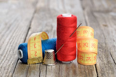 Spools of thread, needle, measuring tape and thimble Stock Images